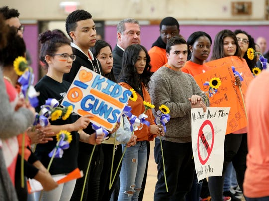 Students at Lincoln High School in Yonkers hold sunflowers
