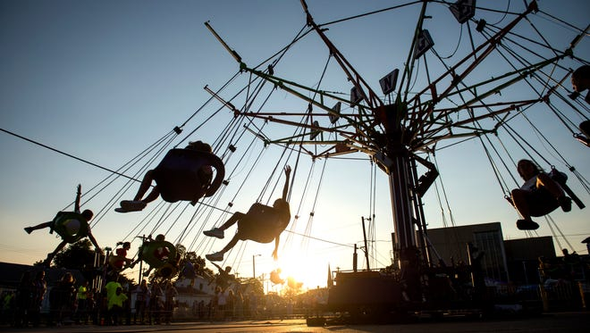 "Children ride the ""swinger"" ride during the Holy Name Fall Festival at Holy Name Elementary School in Henderson, Ky., on Friday, Sept. 8, 2017."