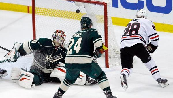 The game-winning shot by Chicago Blackhawks right wing Patrick Kane (88) gets past Minnesota Wild goalie Ilya Bryzgalov, left, of Russia, in front of Wild left wing Matt Cooke (24) during overtime of Game 6 of an NHL hockey second-round playoff series