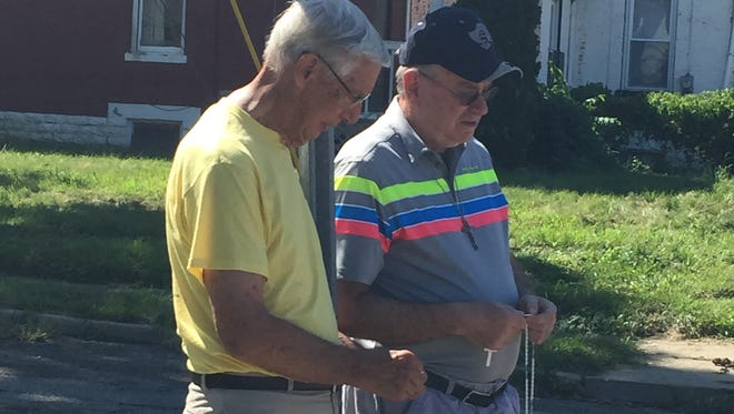 Dick McConn, 78, (left) and Charlie Pfizenmayer, 66, (right) praying the rosary near a double homicide in Madisonville on Saturday.