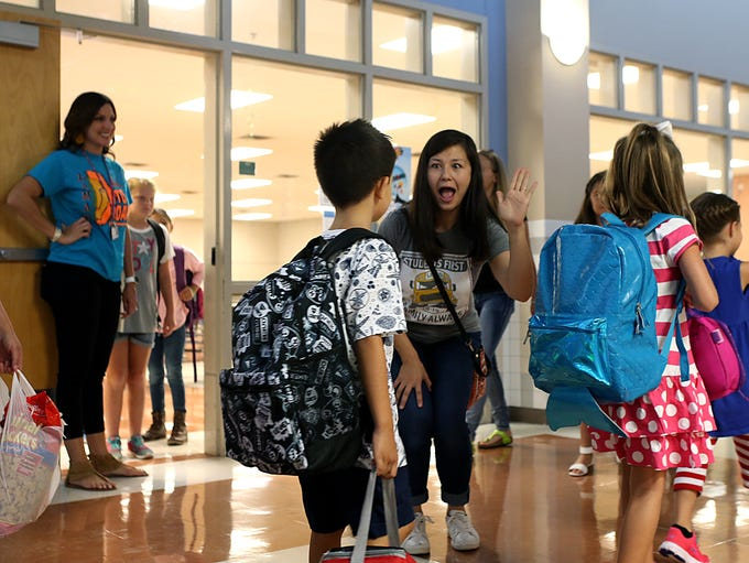 Staff give out high fives to students at Lamar Elementary