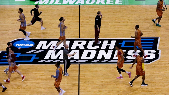 Winthrop basketball coach Pat Kelsey (white-striped pants) directs his team's practice before the first round of the NCAA Tournament at the BMO Harris Bradley Center in Milwaukee.