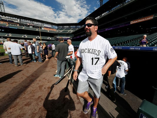 "FILE - In this Sept. 15, 2017, file photo, retired Colorado Rockies first baseman Todd Helton (17) steps out of the dugout as members of the Rockies' 2007 Word Series team look on during batting practice before the Rockies host the San Diego Padres in a baseball game in Denver. Helton now regularly drives his two daughters to school or activities back home in Tennessee, a huge life change for Colorado's former All-Star first baseman. In fact, a daunting and overwhelming adjustment initially. ""It was hardest thing I've ever done in my life,"" Helton shared. (AP Photo/David Zalubowski, File)"