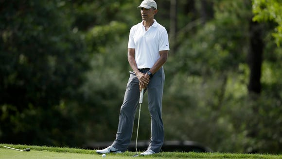 President Obama stands on the edge of a green while