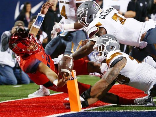 Arizona quarterback Brandon Dawkins dives and places