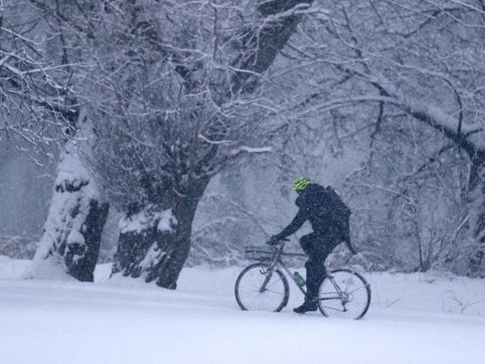 A man rides through Genesee Valley Park in Rochester as snow falls on Tuesday, Dec. 12, 2017.