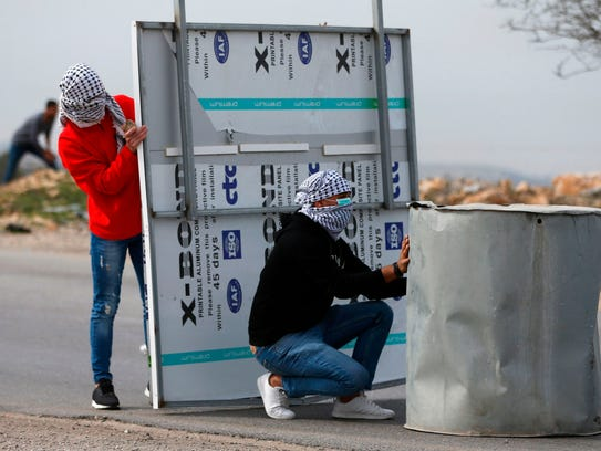Palestinian protestors take cover during clashes with