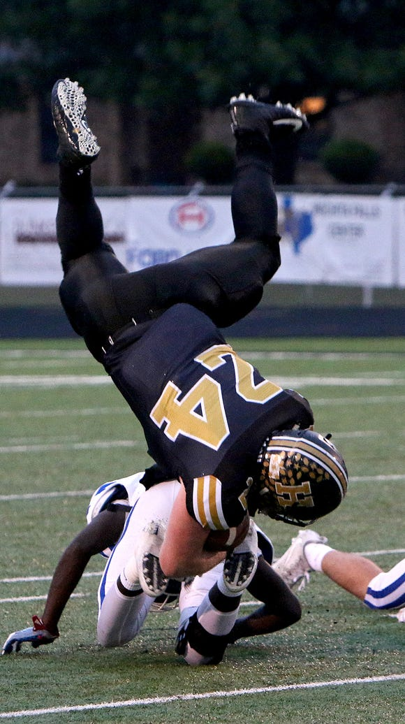 Henrietta quarterback Zack West (24) is upended by