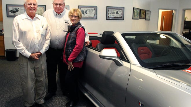 Bob Reed, from left, stands with Jim Barkau and Gerry Reed, Bob's wife, during his birthday recognition on Saturday at J.H. Barkau & Sons in Freeport. Reed celebrated his 83rd birthday and is going strong as a car salesman for the dealership.