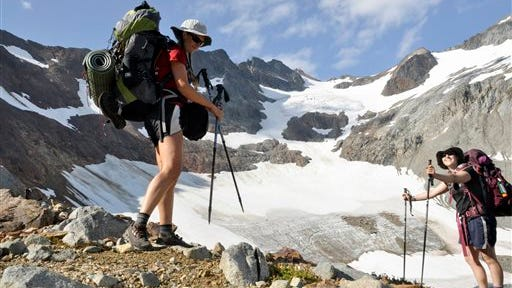 Holly Weiler, left, and Samantha Journot of the Spokane Mountaineers hike past Lyman Glacier as they head toward Spider Gap to complete a loop backpacking trek in Washington state's Glacier Peak Wilderness. The U.S. Forest Service is proposing rules that restrict filming and photography by media organizations and others in more than 100 million acres of the nation's wilderness, Wednesday.