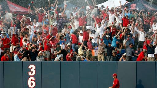 Jacksonville State outfielder Griff Gordon  takes a slow walk past the outfield wall as fans celebrate a sixth inning home run by Ole Miss' Sikes Orvis during an NCAA college baseball regional tournament game in Oxford, Miss., Saturday, May 31, 2014. (AP Photo/Rogelio V. Solis)