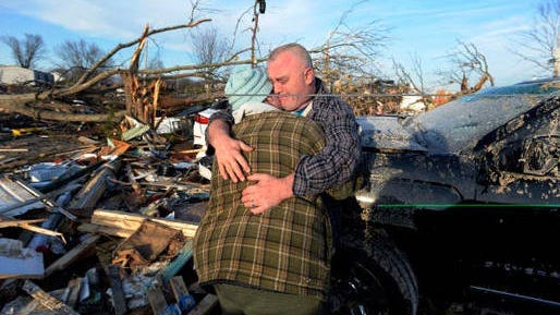 Charles Williams cries as he comforts his wife, Tamara, after a tornado destroyed their home on Tuesday, March 3, 2020, in Cookeville, Tenn.