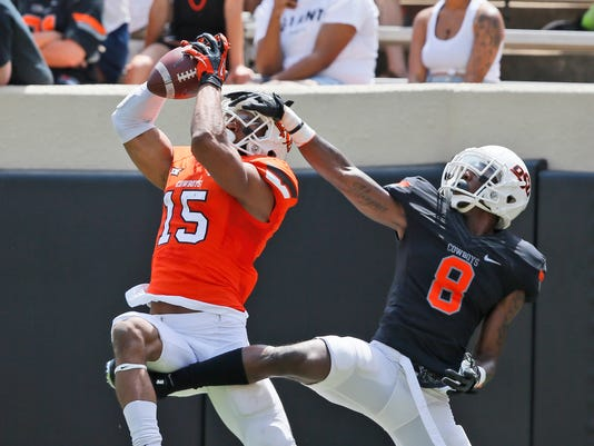 Oklahoma State wide receiver Chris Lacy (15) catches a pass in front of cornerback Rodarius Williams (8) during an intrasquad spring NCAA college football game in Stillwater, Okla., Saturday, April 15, 2017. (AP Photo/Sue Ogrocki)