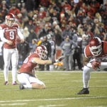 Arkansas kicker Cole Hedlund lines up one of his six PAT kicks while holder Matt Emrich readies for the snap during the Razorbacks' 51-50 loss to Mississippi State on Saturday in Fayetteville.
