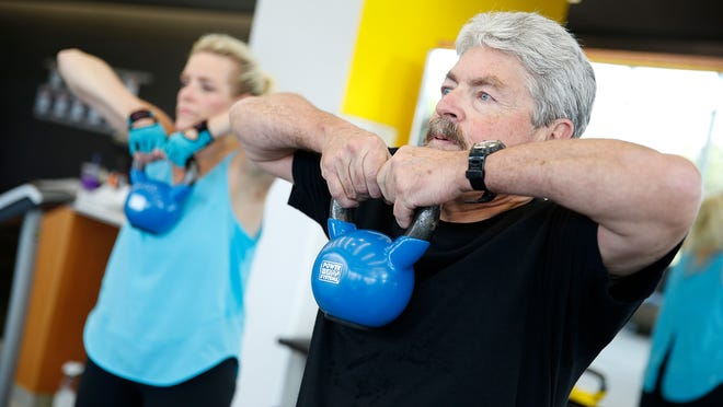 James Hill and Holly Wyatt, co-authors of 'State of Slim,' believe exercise is very important in controlling weight. The two recently work out together with kettle balls at the Anschutz Health and Wellness Center in Aurora, Colo.