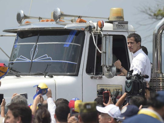 Venezuelan opposition leader Juan Guaido gestures from the side of a truck, at the Colombian side of the Tienditas International Bridge in Cucuta, before an attempt to cross humanitarian aid over the border into Venezuela, on February 23, 2019.