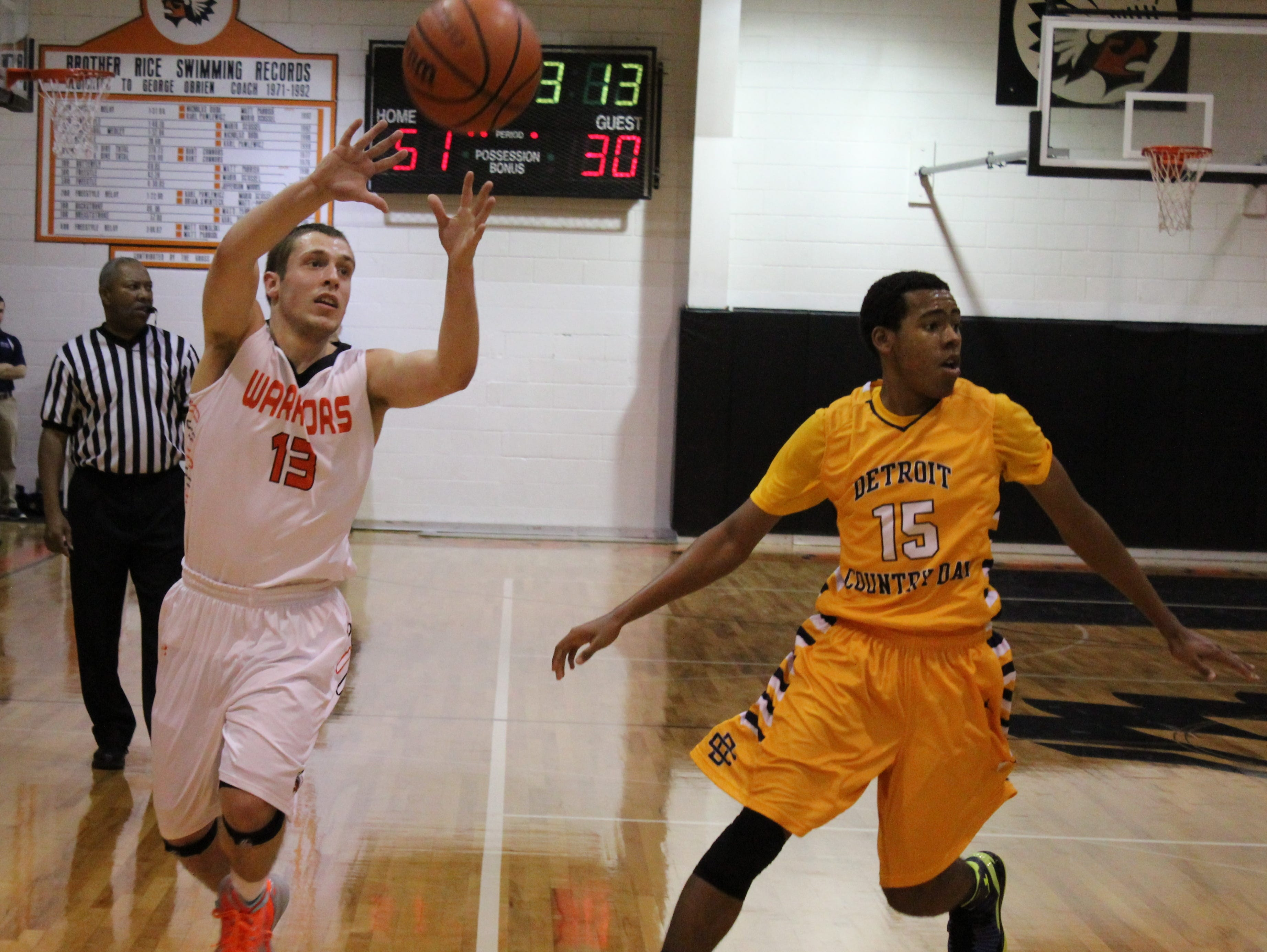 Brother Rice senior guard Dominic Downs (13) slips the ball past Country Day defender Devin Beach (15) in Friday's game played at Rice. The Warriors won, 77-51.