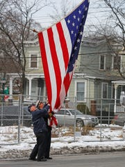 Capt. Lou Barber of the Lake Mohegan Fire Department and Deputy Chief John Pappas of the Peekskill Fire Department take down the flag after a ground breaking ceremony for the new Peekskill firehouse.
