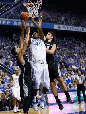 Kentucky Wildcats center Dakari Johnson (44) shoots the ball against Providence Friars guard Kris Dunn (3) and forward Carson Desrosiers (33) during the first half at Rupp Arena.