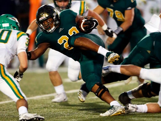 Catholic's Joe Fluker (22) runs for yardage during