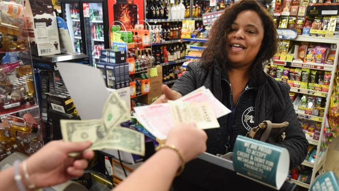 Tania Perkins of Waterford buys Powerball tickets on Friday at Amori's Market in Madison Heights.