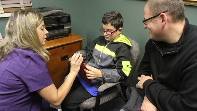 A smile slowly spreads across the face of Colton Goff, 10, as Dr. Kimberly Kelley, left, adjusts settings on his assisted-hearig device. Dad Dave Goff is at right. The device was activated during a recent visit to Livingston Hearing Center in Hartland Township.
