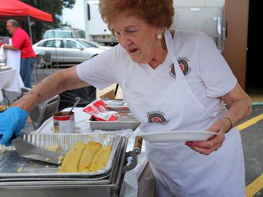 Leona Lisoski, 92, a ladies auxiliary member at the American Polish Century Club, serves traditional food including nalesniki, golabki, kupusta and pierogi during the festival on Sunday.