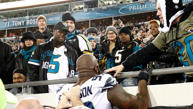 Seattle Seahawks defensive tackle Quinton Jefferson, center, tries to climb up in the stands after Jacksonville Jaguars fans threw objects at him in the closing moments of an NFL football game, Sunday, Dec. 10, 2017, in Jacksonville, Fla.