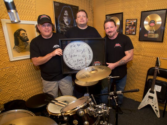 Old Bridge Militia members (L to R) Joe Chimienti of Columbus, Shawn Morales of Jackson and Ray Dill of Old Bridge display a drum skin autographed by Metallica members, Thursday, February 4, 2016, in Dill's drum room in Old Bridge.