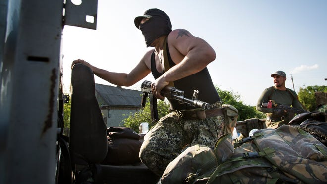 Pro-Russian gunmen get ready to fight Ukrainian national troops at a checkpoint outside Slovyansk, Ukraine, on May 15.