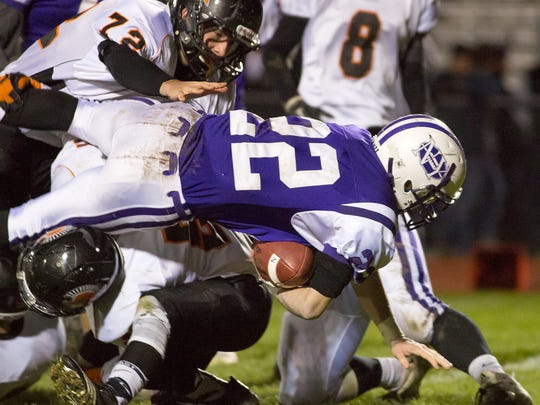 Northern's Michael Kearney dives over a York Suburban defender.  Northern York defeated York Suburban 30-16 in the first round of District III playoffs Friday, Nov. 13, 2015.