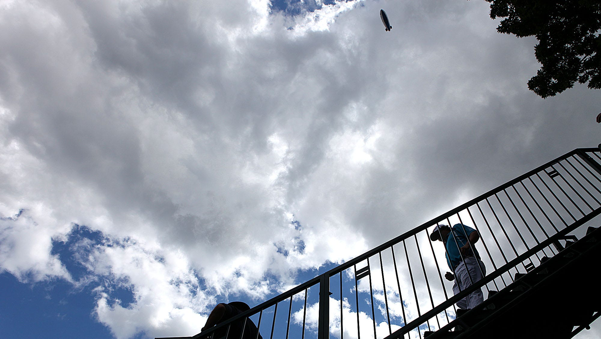 Jaosn Dufner walks down the steps to the first hole as the blimp hovers above.