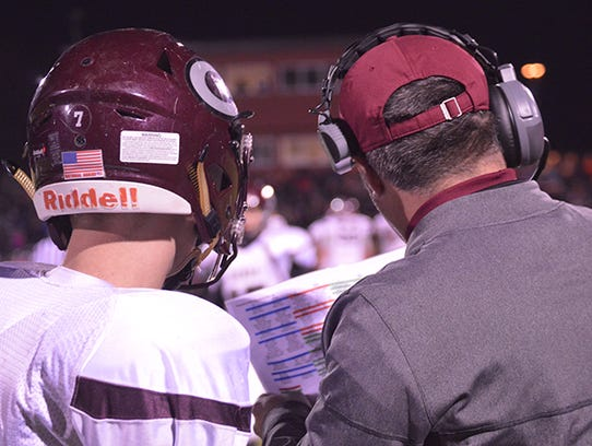 Genoa quarterback Caleb McGeorge checks with coach