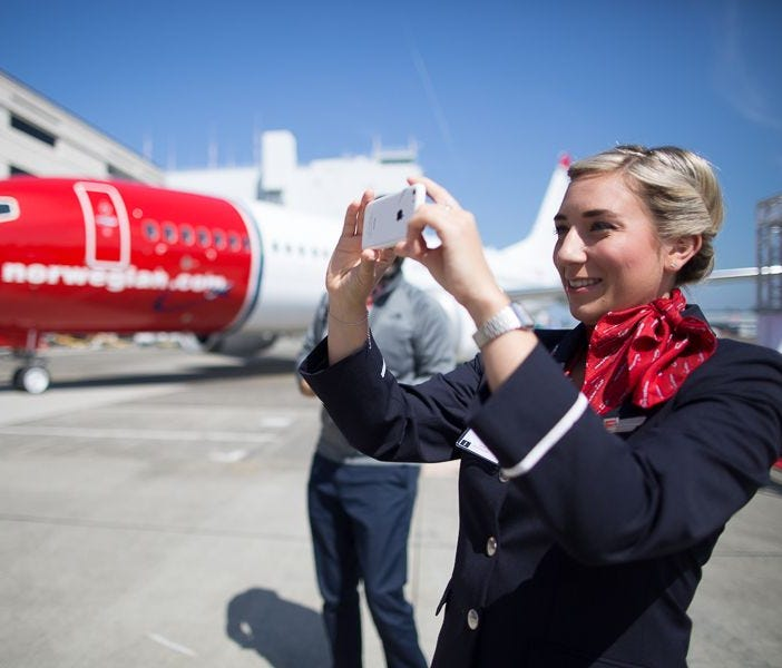 A Norwegian Air crew member captures images of the 737 Max delivery ceremony on her cellphone in Seattle on June 29, 2017.