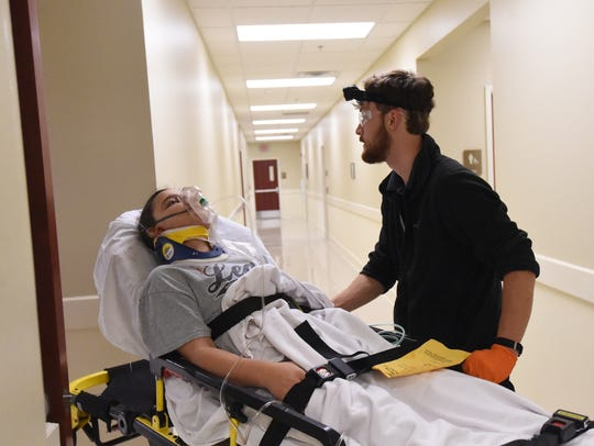 A student transports a volunteer during a mass casualty drill at Arkansas State University-Mountain Home Wednesday evening. The drill unfolded in a parking lot.