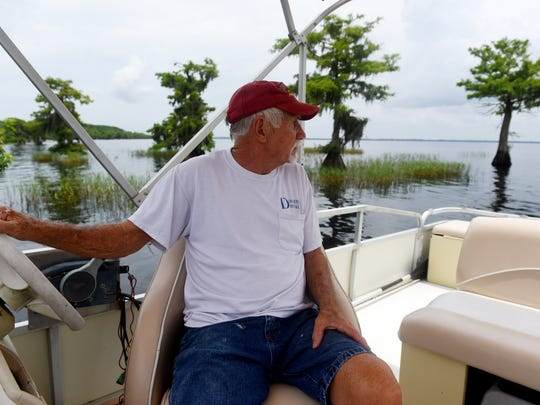 """Don Buhr, a permanent resident on Blue Cypress Lake, guides his boat Thursday, May 31, 2018, through the cypress trees that line the shore. The lake in northwest Indian River County is being polluted by runoff from nearby Pressley Ranch that fertilizes its pastures with human sewage sludge, according to several prominent environmentalists. """"This area is a gem in the state of Florida, some of the most beautiful you'll ever see,"""" said Buhr. """"Can you imagine living here all these years telling people that this is the cleanest water in the state then come to find out it's all a lie?"""""""