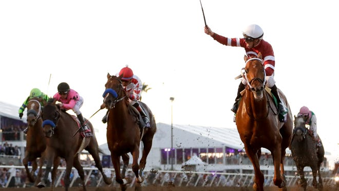 Jockey Florent Geroux celebrates after riding Gun Runner to victory in the Breeders' Cup Classic on Saturday at Del Mar.