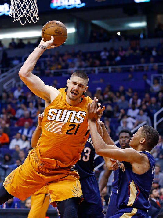 Phoenix Suns center Alex Len (21) gets fouled by New Orleans Pelicans guard Tim Frazier, right, during the second half of an NBA basketball game Sunday, Dec. 11, 2016, in Phoenix. The Pelicans won 120-119 in overtime. (AP Photo/Ross D. Franklin)