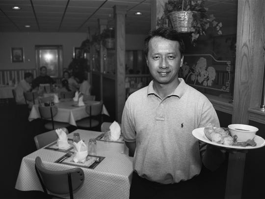 James Ta, owner of Saigon Cafe, holds a plate of spring rolls.