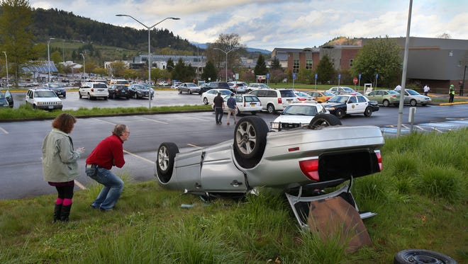 People look as a car after it was flipped by a funnel cloud that cut through a parking lot at Lane Community College in Eugene, Ore., Tuesday, April 14, 2015. No injuries were reported. (Brian Davies/The Register-Guard via AP)