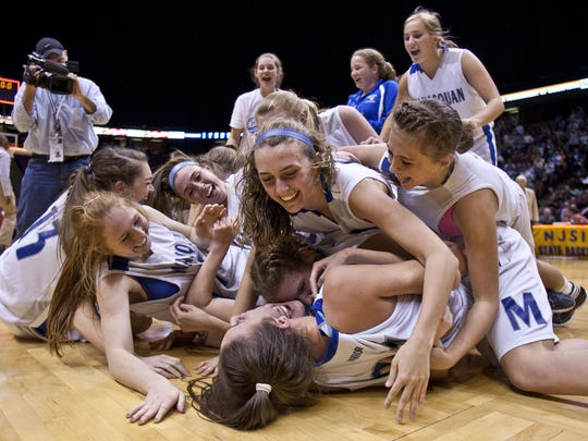 Manasquan Warriors celebrate Tuesday after winning their first NJSIAA Tournament of Champions girls basketball crown at the Izod Center in East Rutherford.