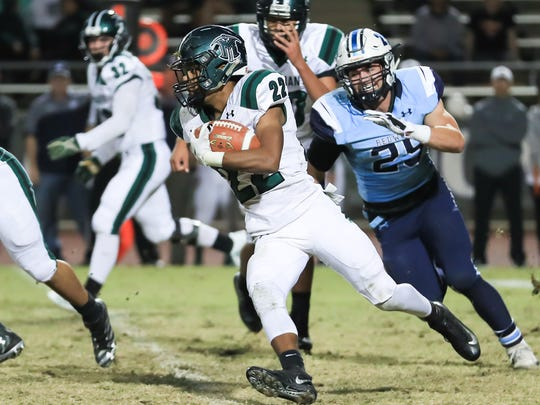 El Diamante's Devontae Freeman (22) runs past Redwood's