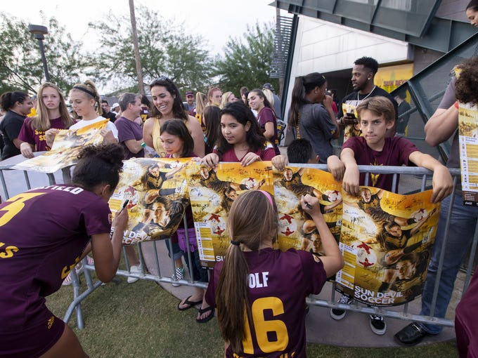 The Arizona State Sun Devils sign autographs following