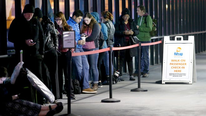 Bremerton commuters wait in the ticket line on the dock for Kitsap Transit's Rich Passage 1 on Wednesday, November 1, 2017.