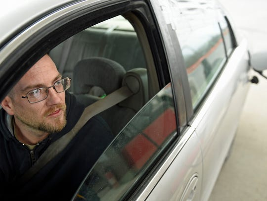 Chris Swanger sits in his car while an attendant pumps