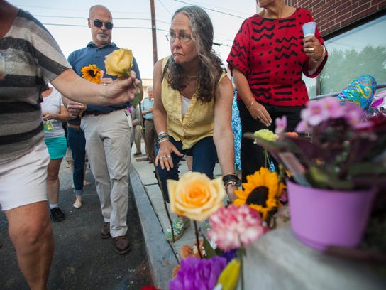 Mourners in Barre place flowers on the ground in memory