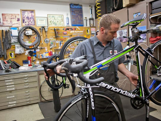 Nathan Talbot performs maintenance on a bike at Bicycles Unlimited.