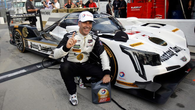 Joao Barbosa poses next to his Cadillac DPi after winning the pole Thursday for the Rolex 24 at Daytona.