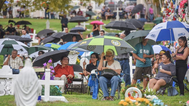 Even with dark clouds looming overhead, family and friends attend an All Souls' Day Mass at the gravesite of loved ones at the Pigo Catholic Cemetery in Anigua on Wednesday, Nov. 2, 2016.