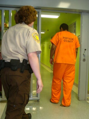 A corrections officer in the Portage County Jail escorts an inmate back to his cell.